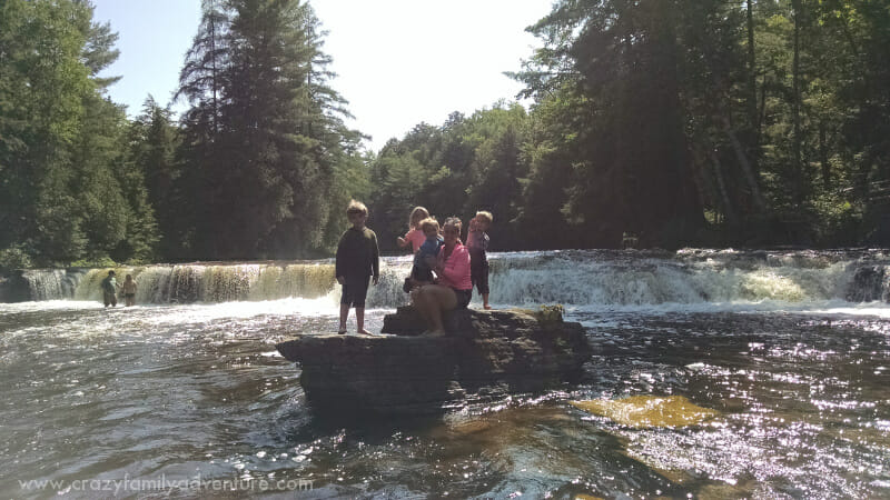 Posing for a picture on a rock in the middle of the river by the falls.